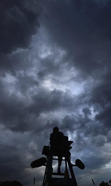 Силуэт судьи на корте №12 напротив дождевых облаков
