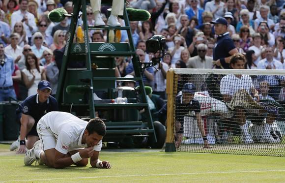 Сербский теннисист Новак Джокович целует корт после победы в финале